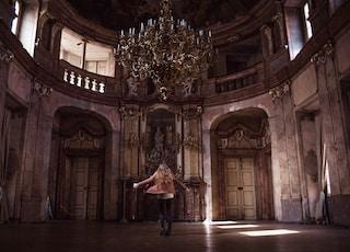 woman standing under gold chandelier indoors