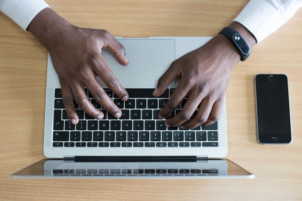 person's hand on MacBook near iPhone flat lay photography