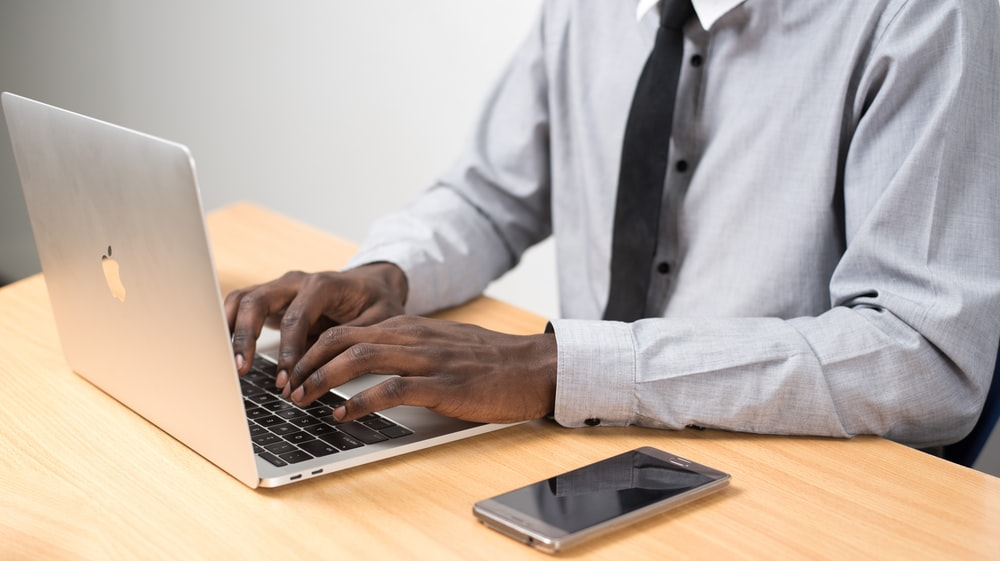 man sits typing on MacBook Air on table