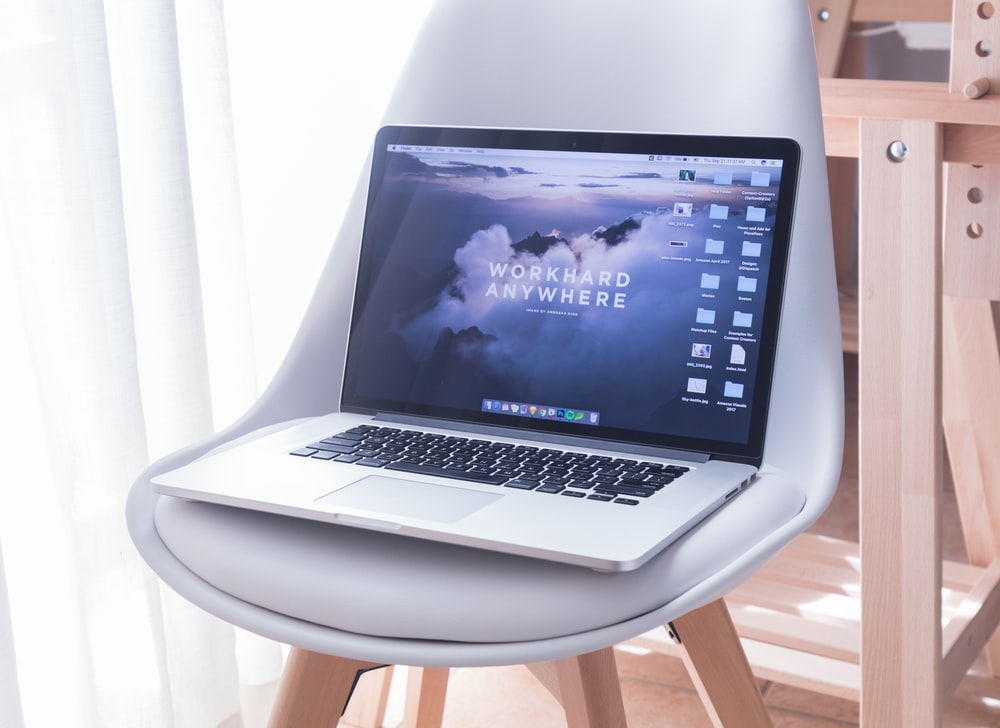 MacBook Pro on white padded chair