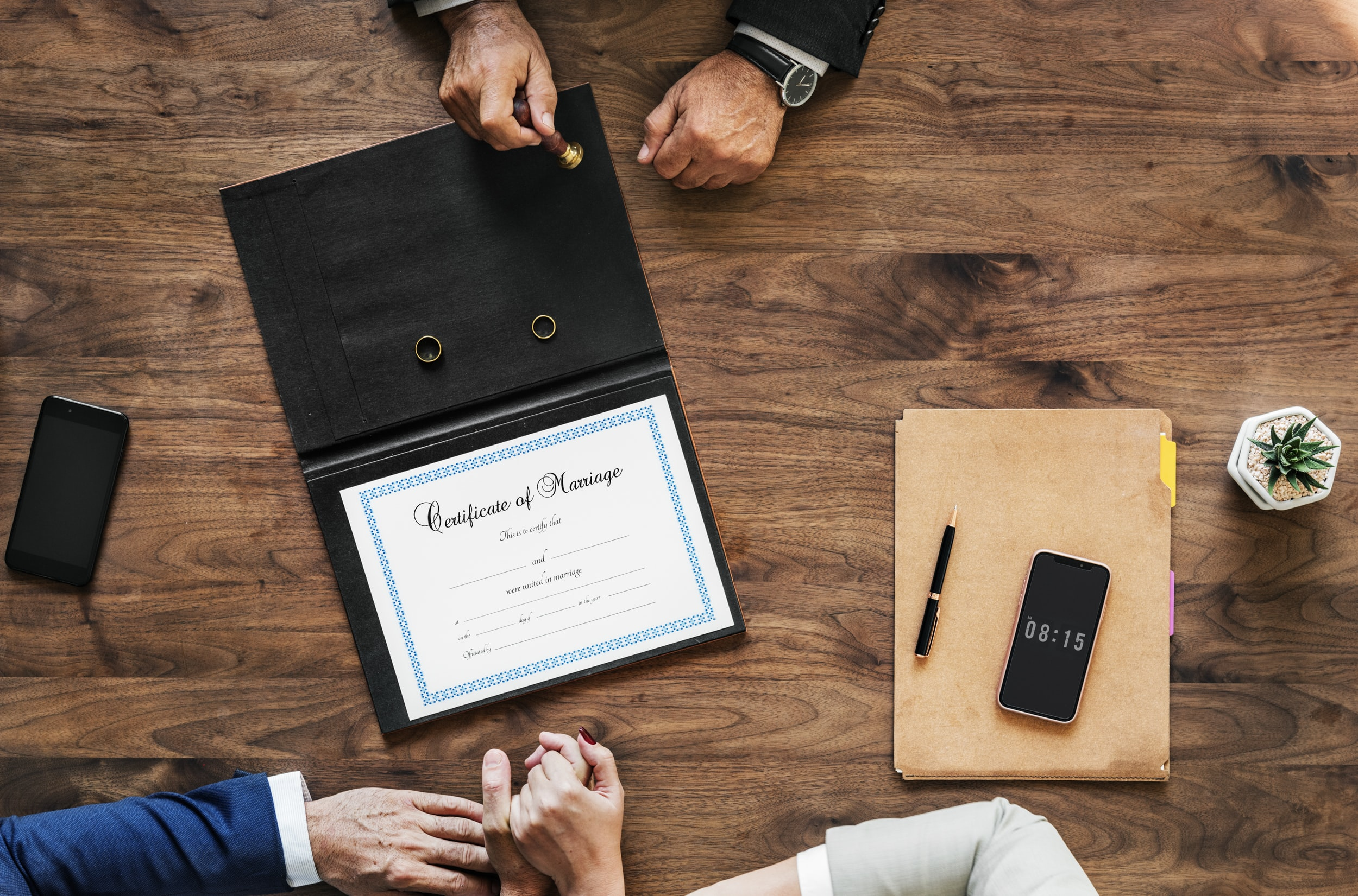 flat lay photography of certificate and folder on table with three people leaning