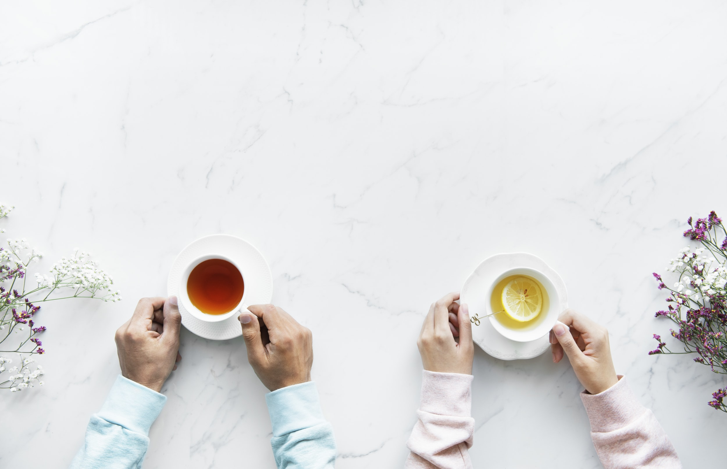 two person holding ceramic mugs