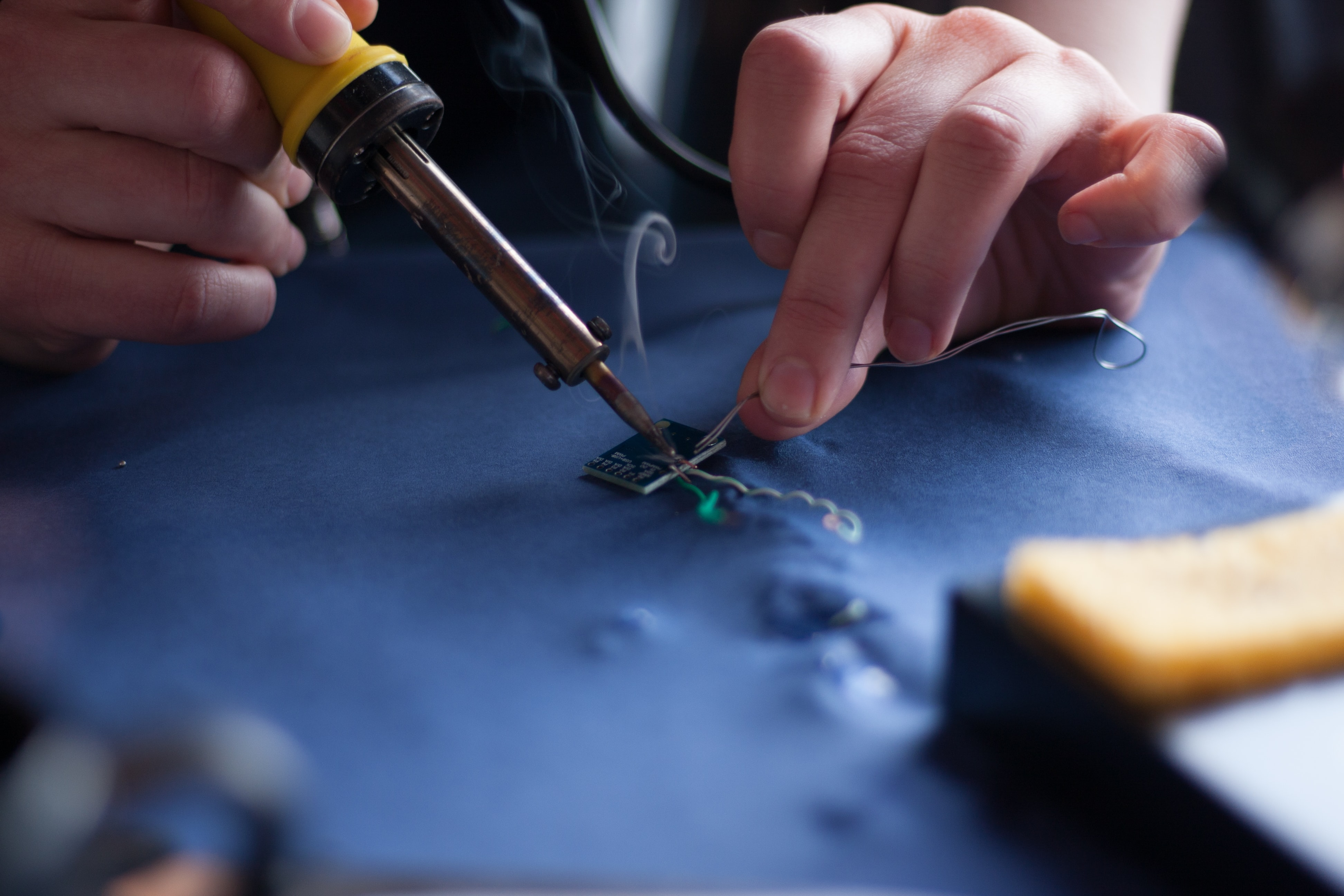 person using soldering iron