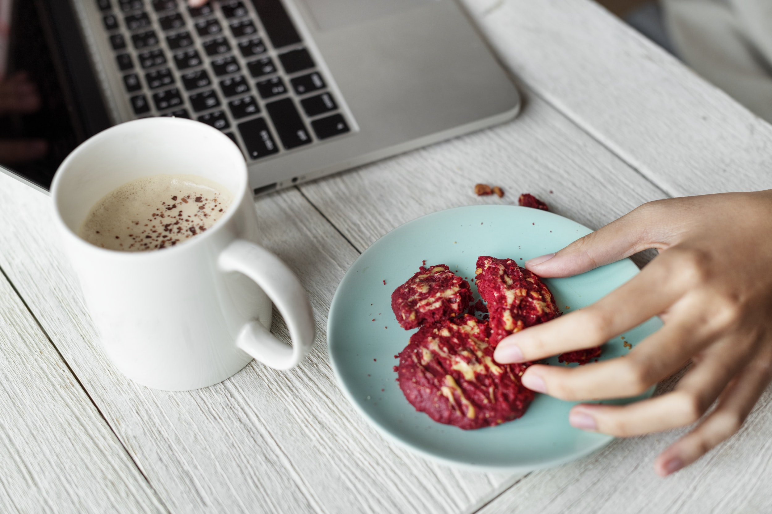 person holding red cookie with laptop on table