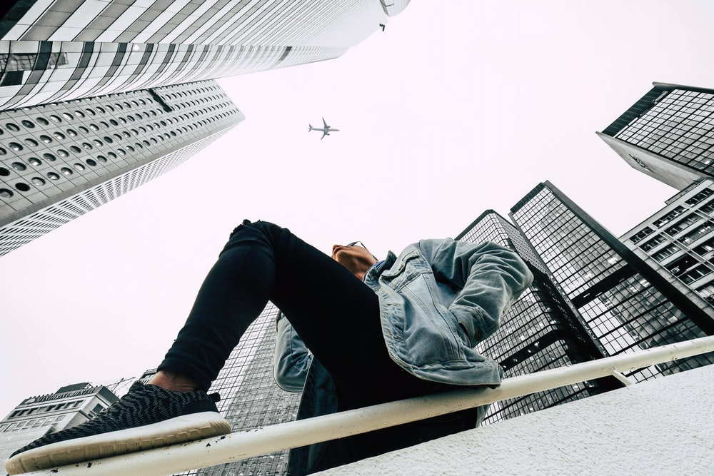 low-angle photography of person wearing blue denim jacket and black pants leaning on white metal railing between curtain wall buildings during daytime