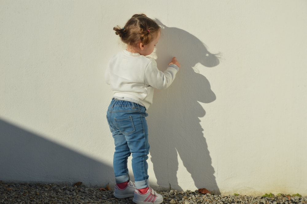 child touching white painted wall during daytime