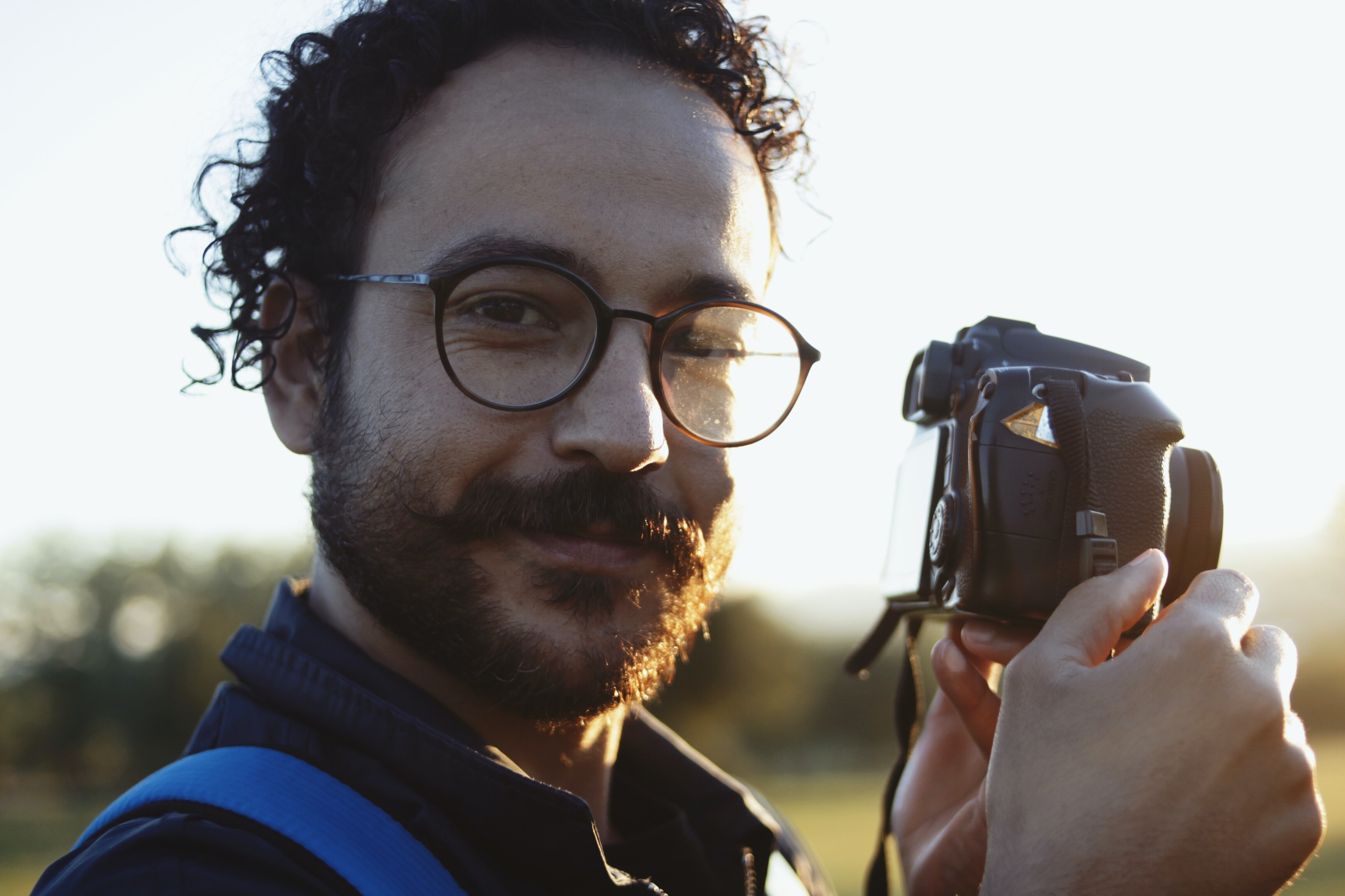 man wearing eyeglasses holding DSLR camera