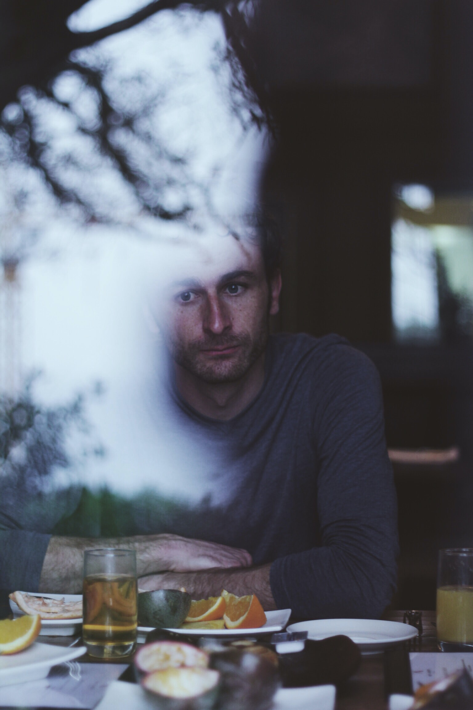 man sitting in front of table with sliced citrus fruit