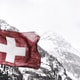 white and red cross flag in front of snow covered mountains