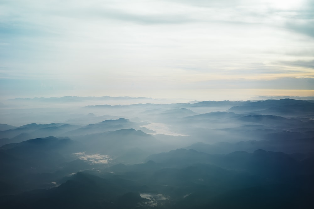 aerial photography of blue mountains surrounded by fogs under white sky at daytime