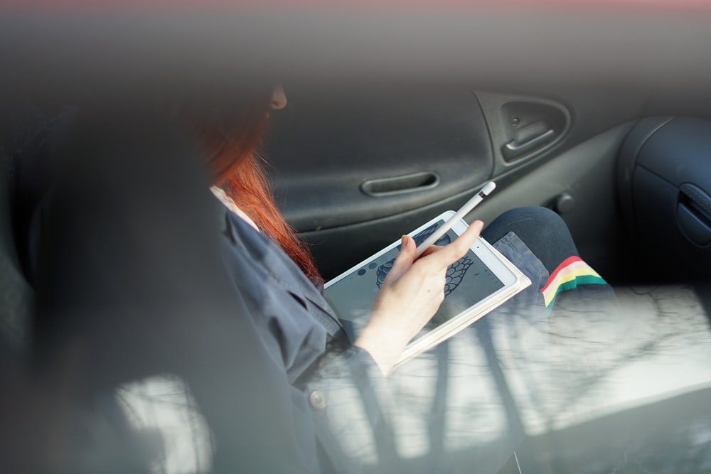 woman holding a Apple Pencil inside black car