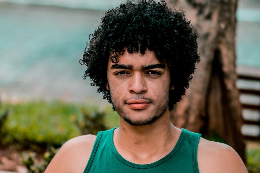 selective focus photo of man wearing green tank top
