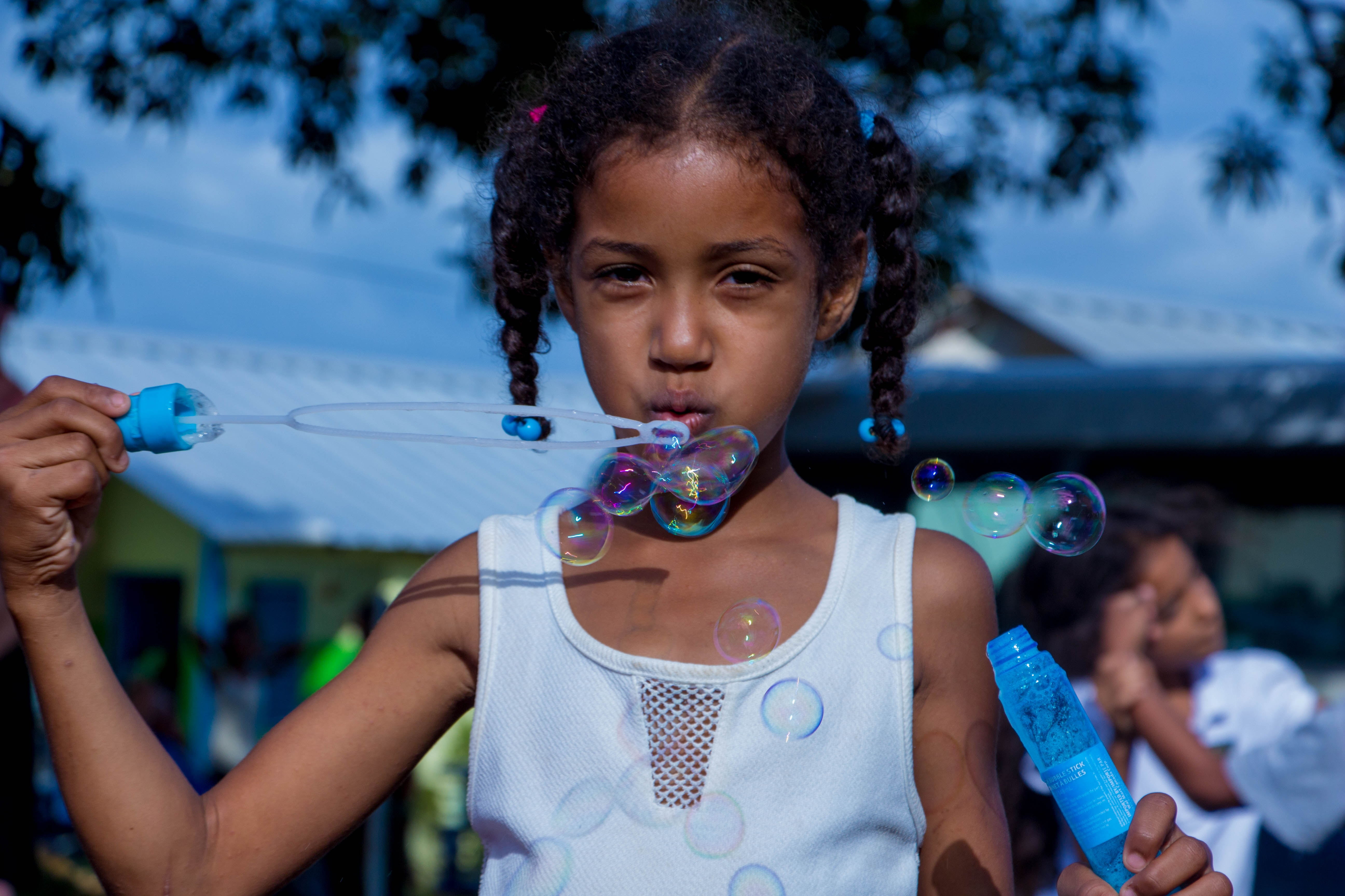 girl in white sleeveless top blowing bubbles