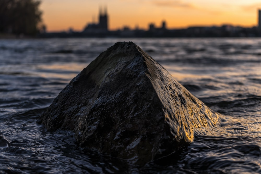 brown rock on body of water at golden hour