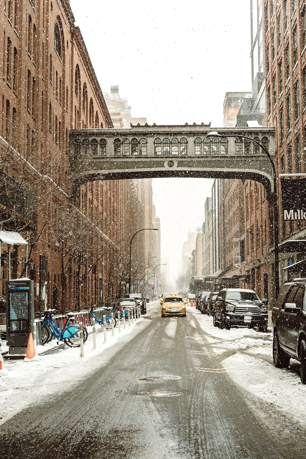 yellow vehicle between brown buildings besides parked vehicles while raining snows