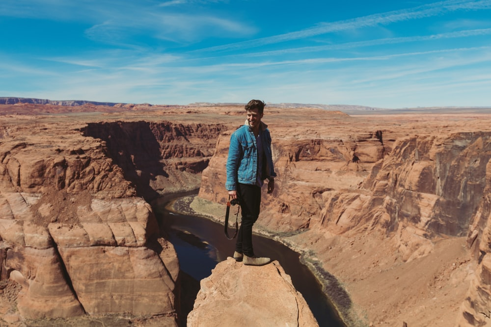 man standing on rocky cliff across hills during daytime