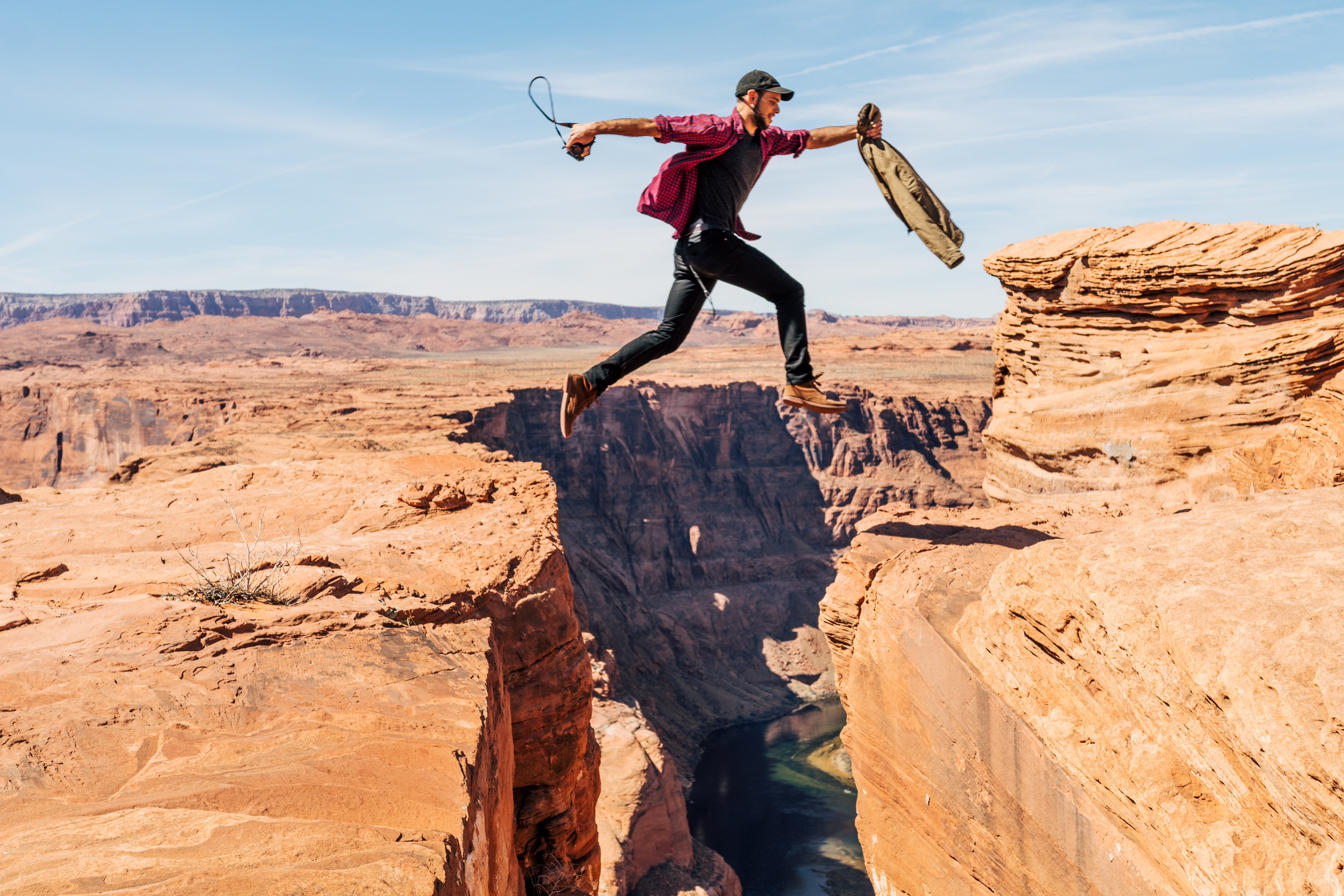 man jumping on rock formation