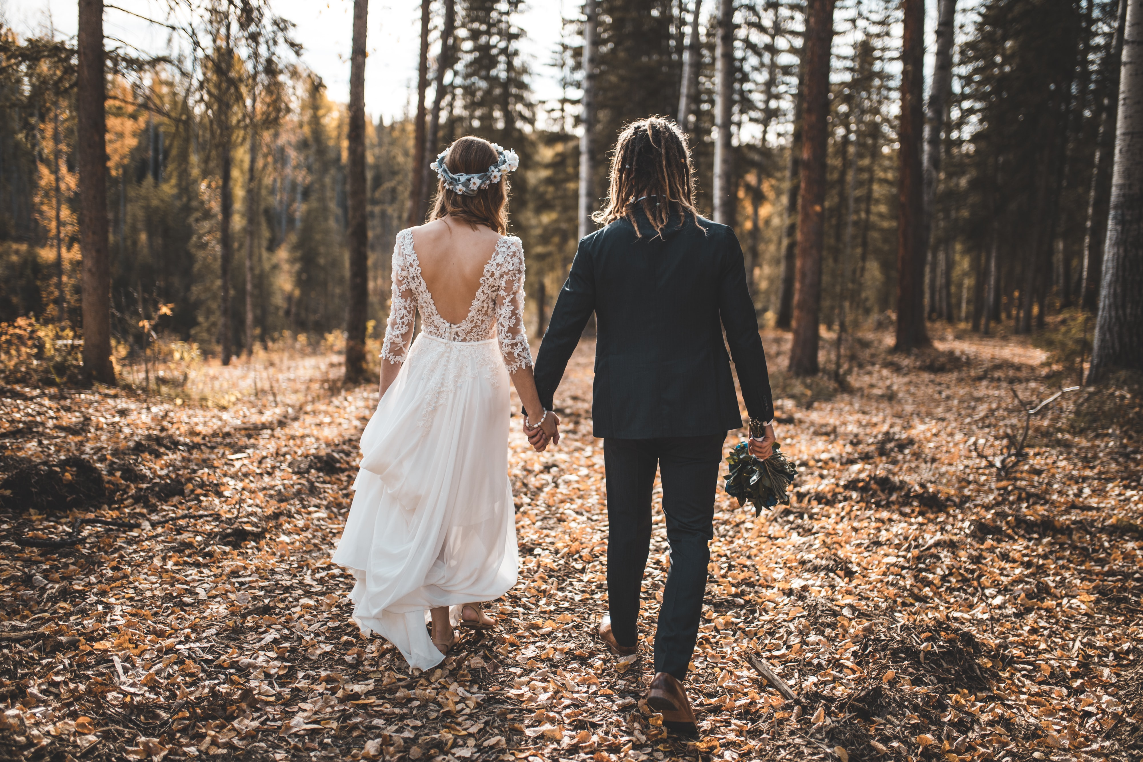 bride and groom walking on leaves covered ground in woods during day