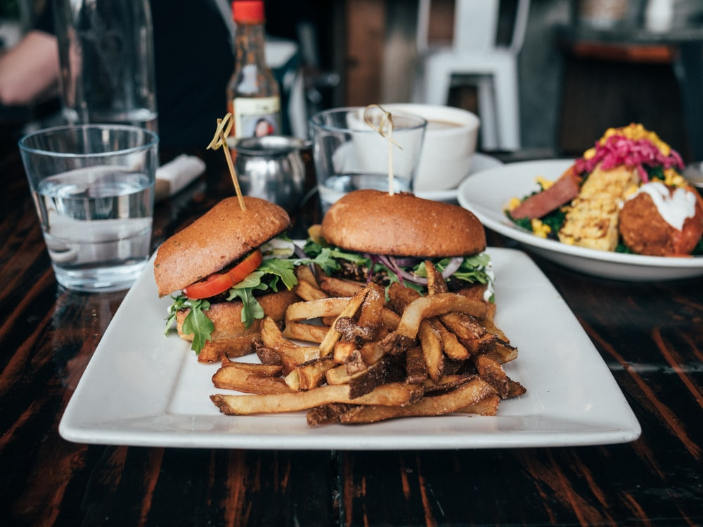 selective focus photo of burgers and fries served on plate