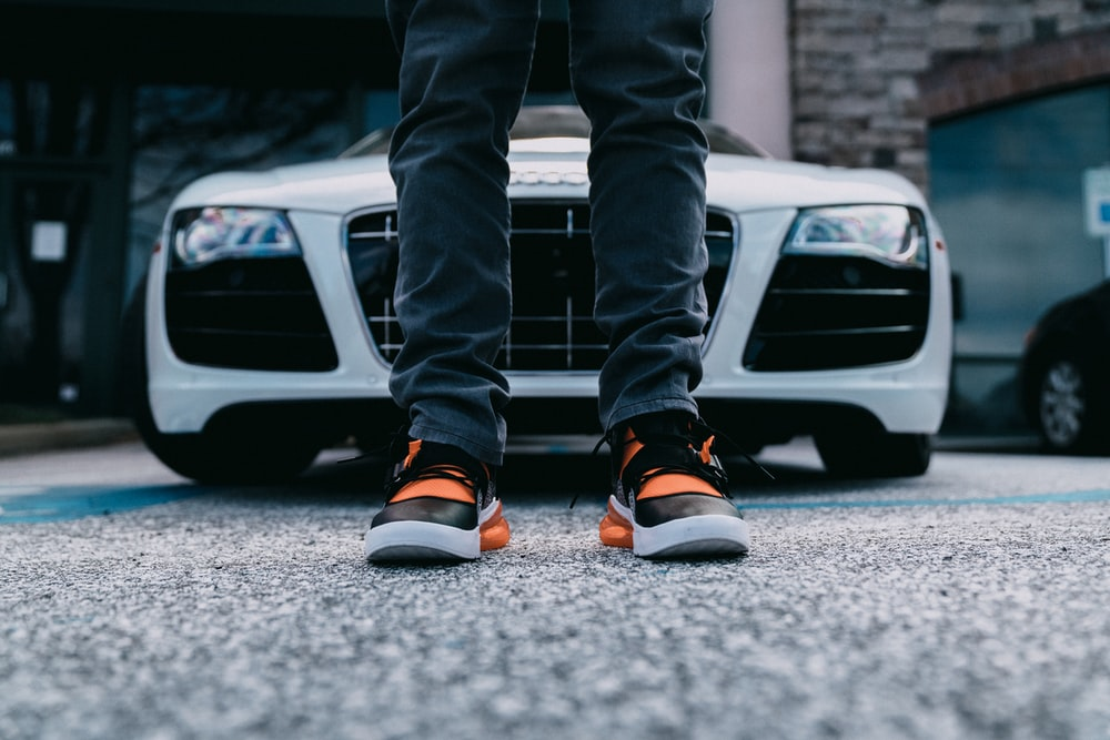 person wearing orange and black shoes behind white car