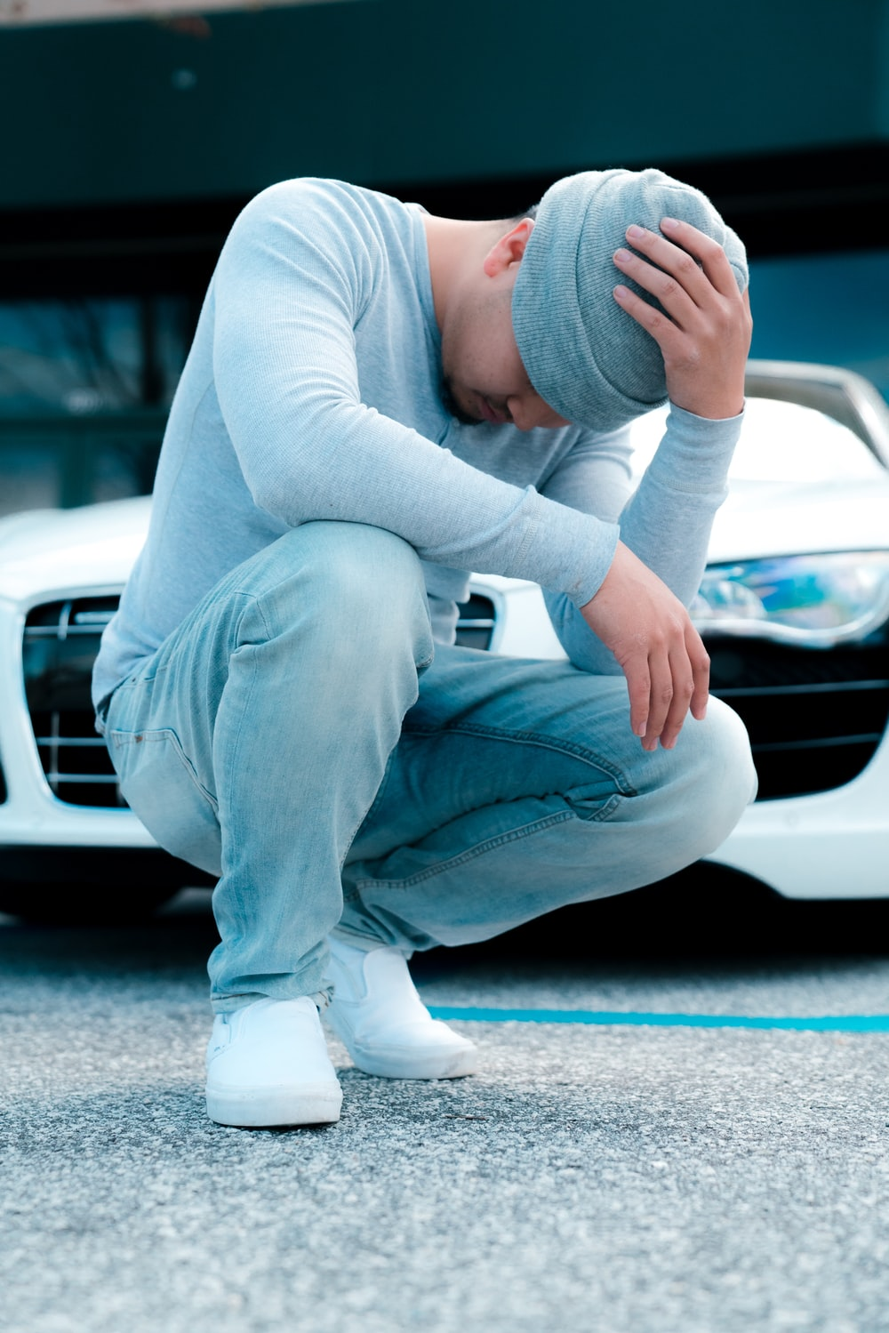 man wearing grey long-sleeved shirt sitting on ground while holding his knit cap