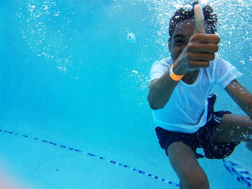 under water photography of boy showing thumb