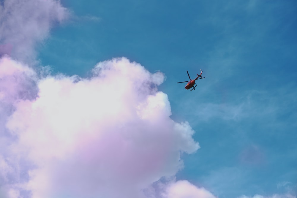 red helicopter on flight about to reach clouds