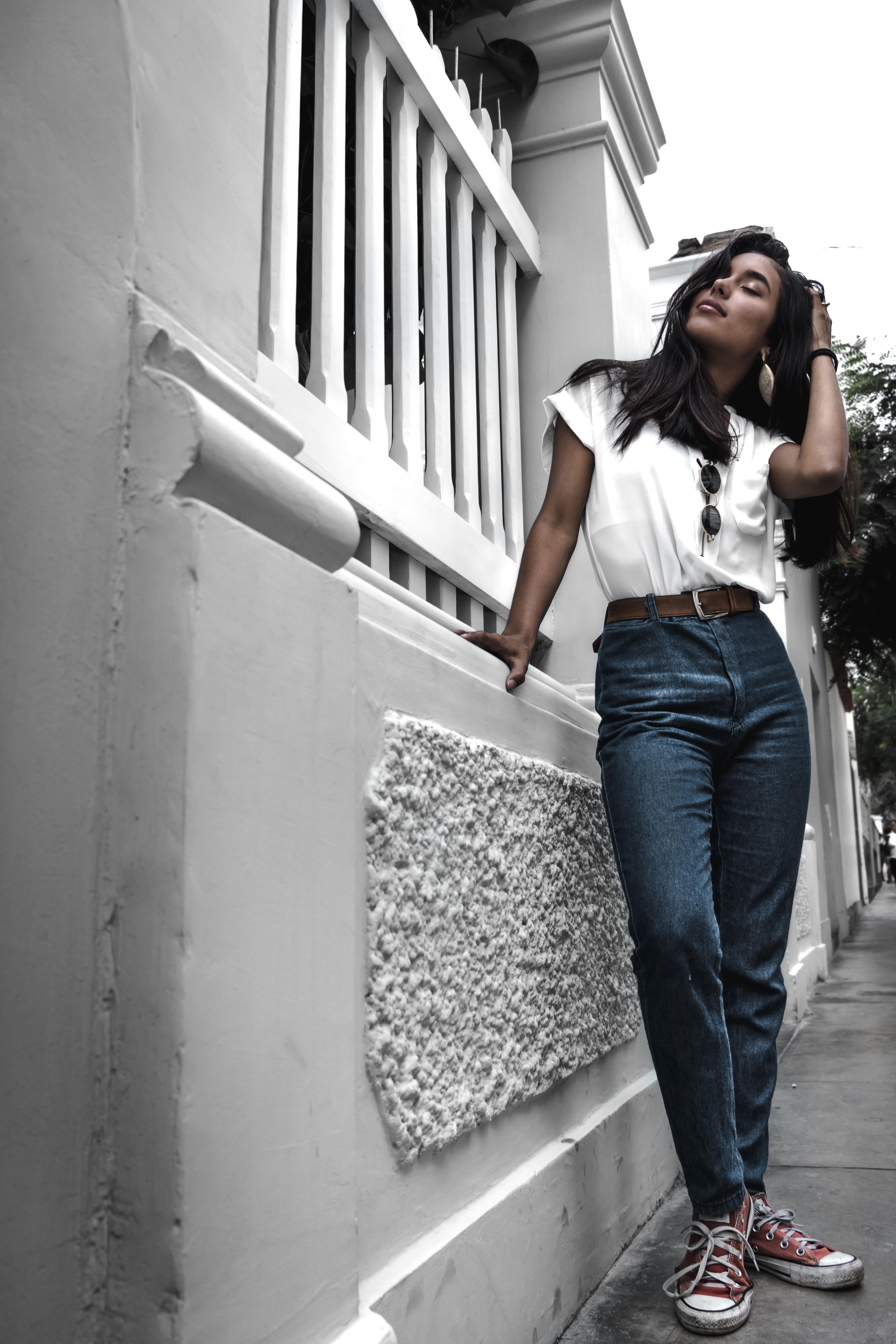 woman wearing white shirt and blue jeans standing beside white wall and holding her hair with her left hand during daytime photo