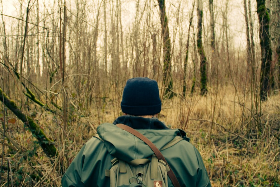 man with backpack walking through forest