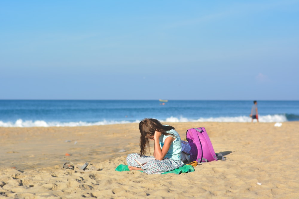 girl sits on shore near purple backpack under blue sky