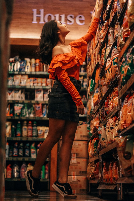woman reaching chip packs inside store