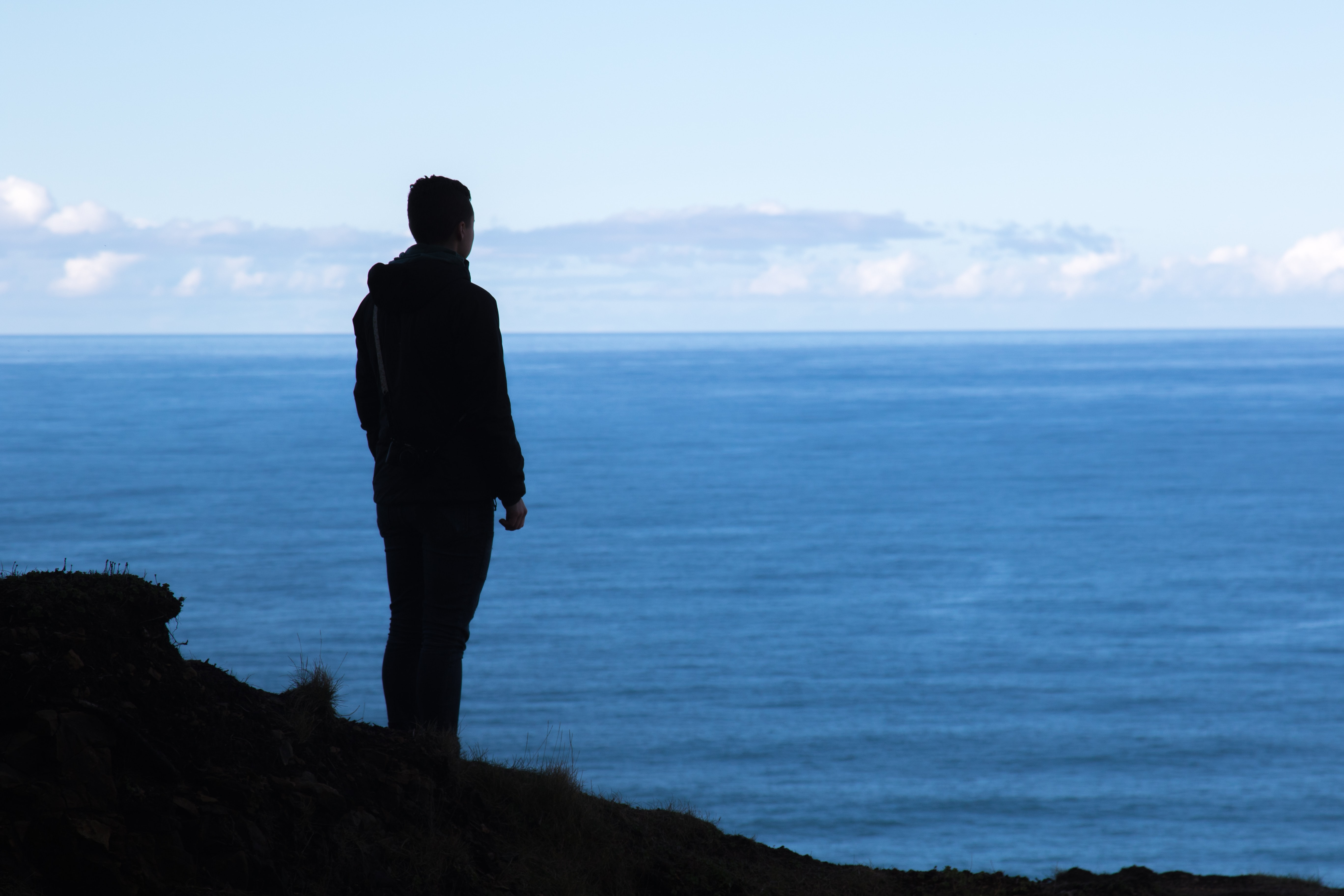 man standing near cliff watching the overview of body of water