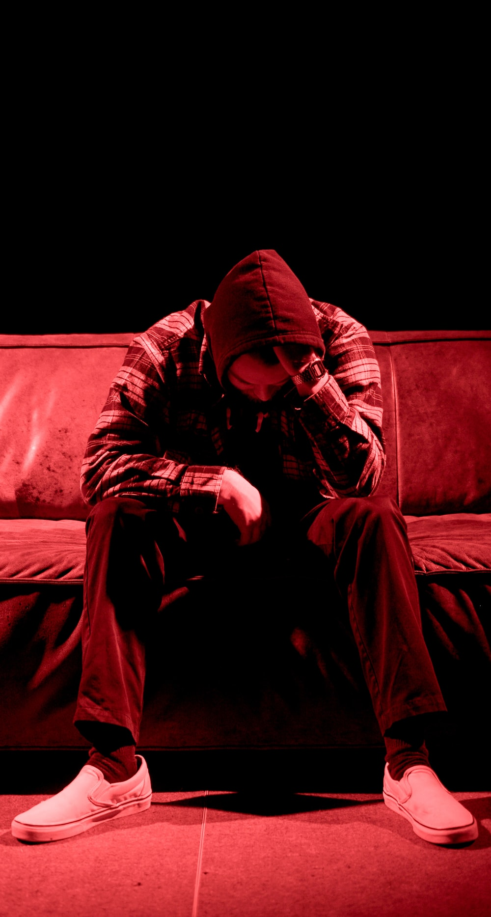man wearing grey hooded jacket sitting on the sofa photography
