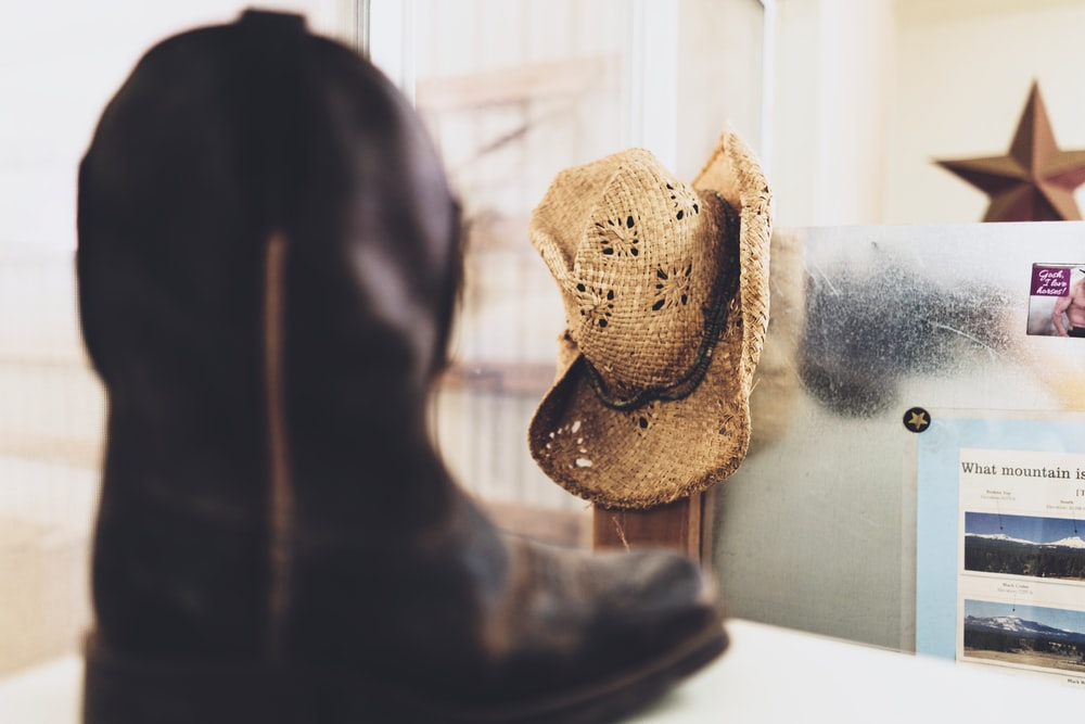 black cowboy boot near brown straw hat on white wall selective-focus photography