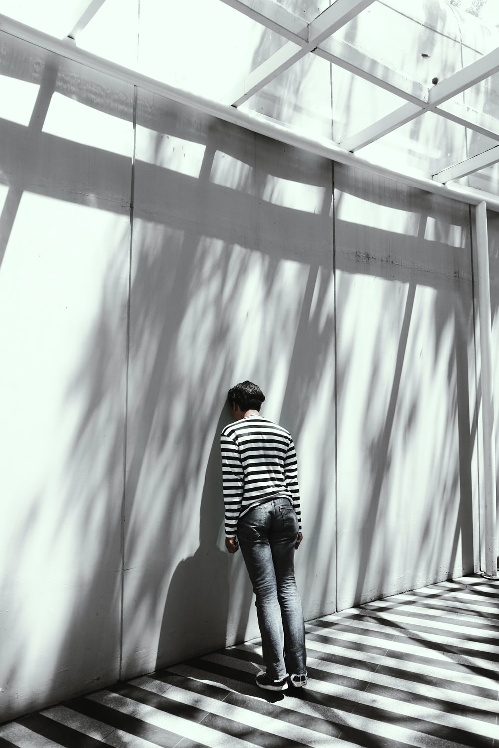 person leaning on white wall