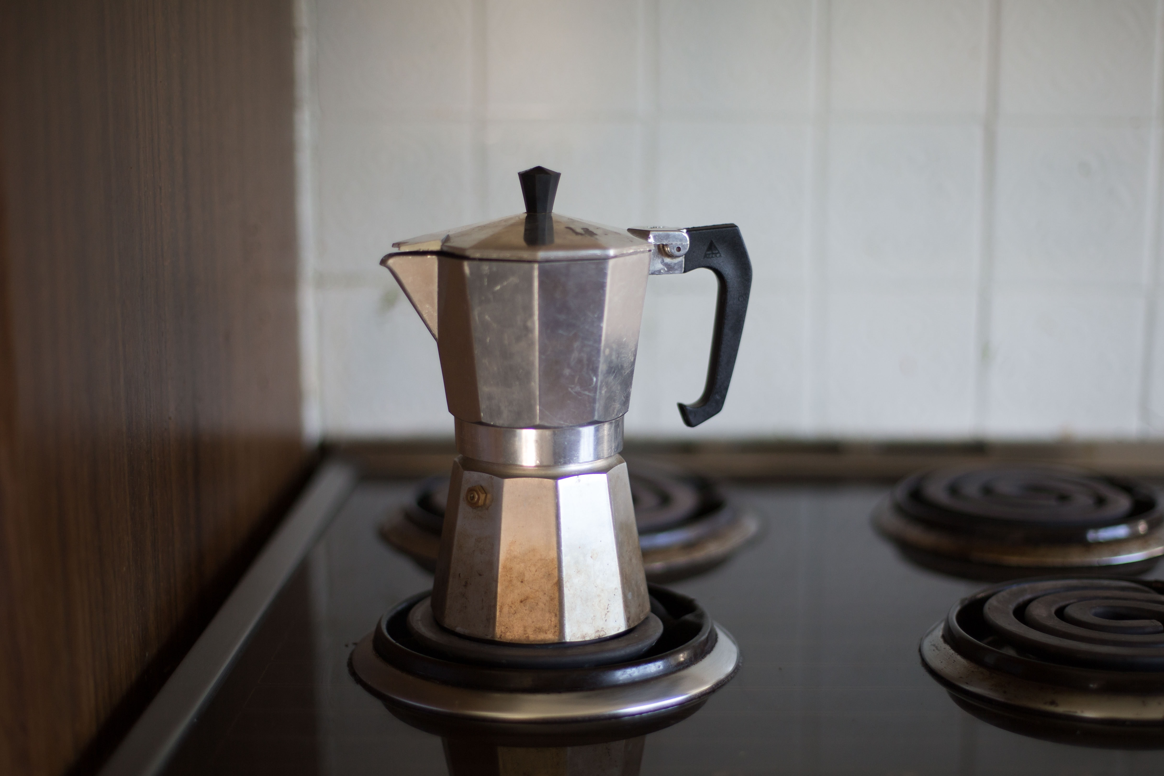 gray moka pot on electric coil stove selective focus photo