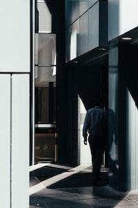 man walking on gray tiled pathway inside building