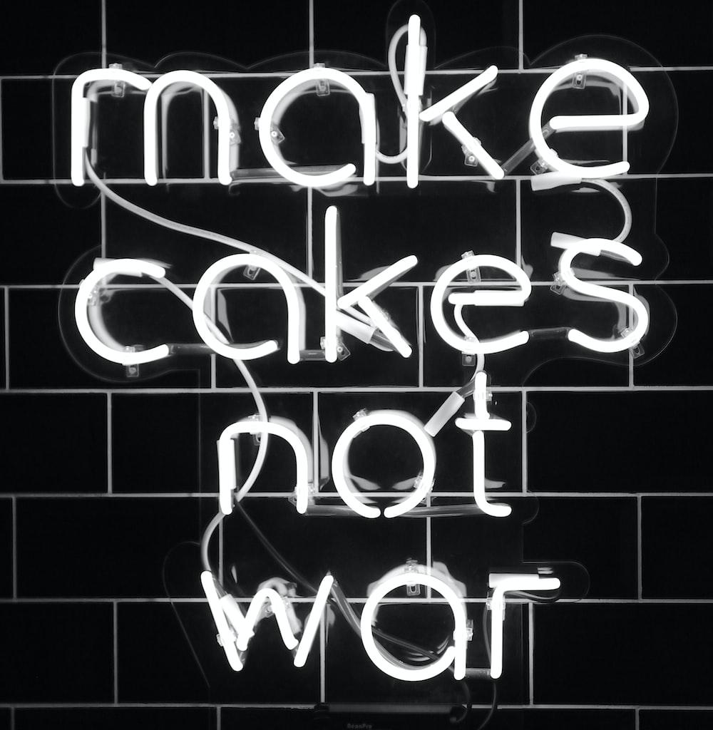 white make cakes not war neon sign