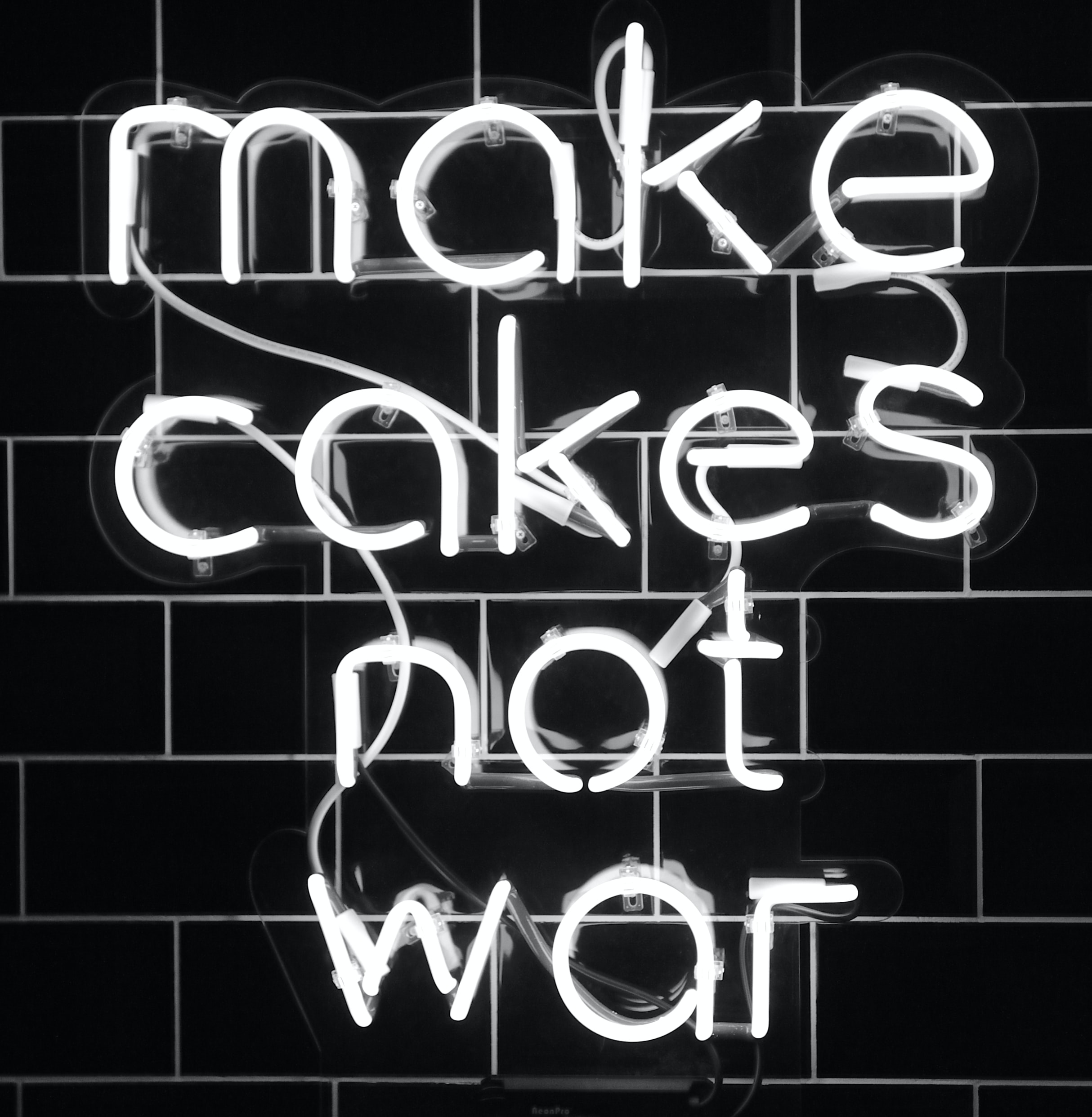 white make cakes not war neon sign