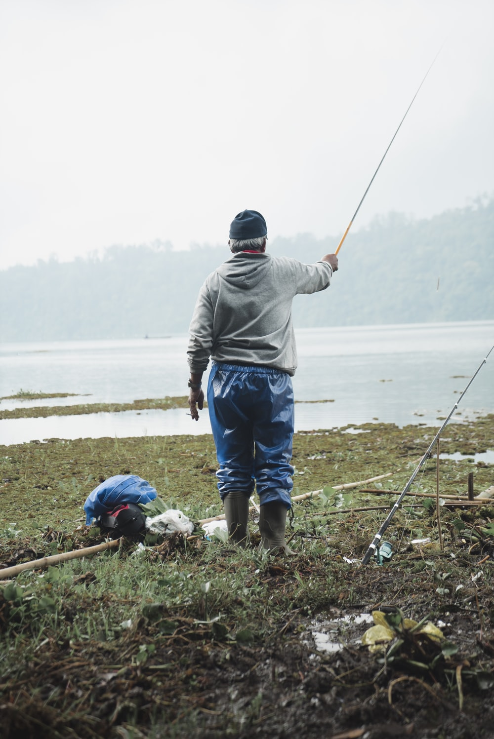 man standing on shore holding fishing rod