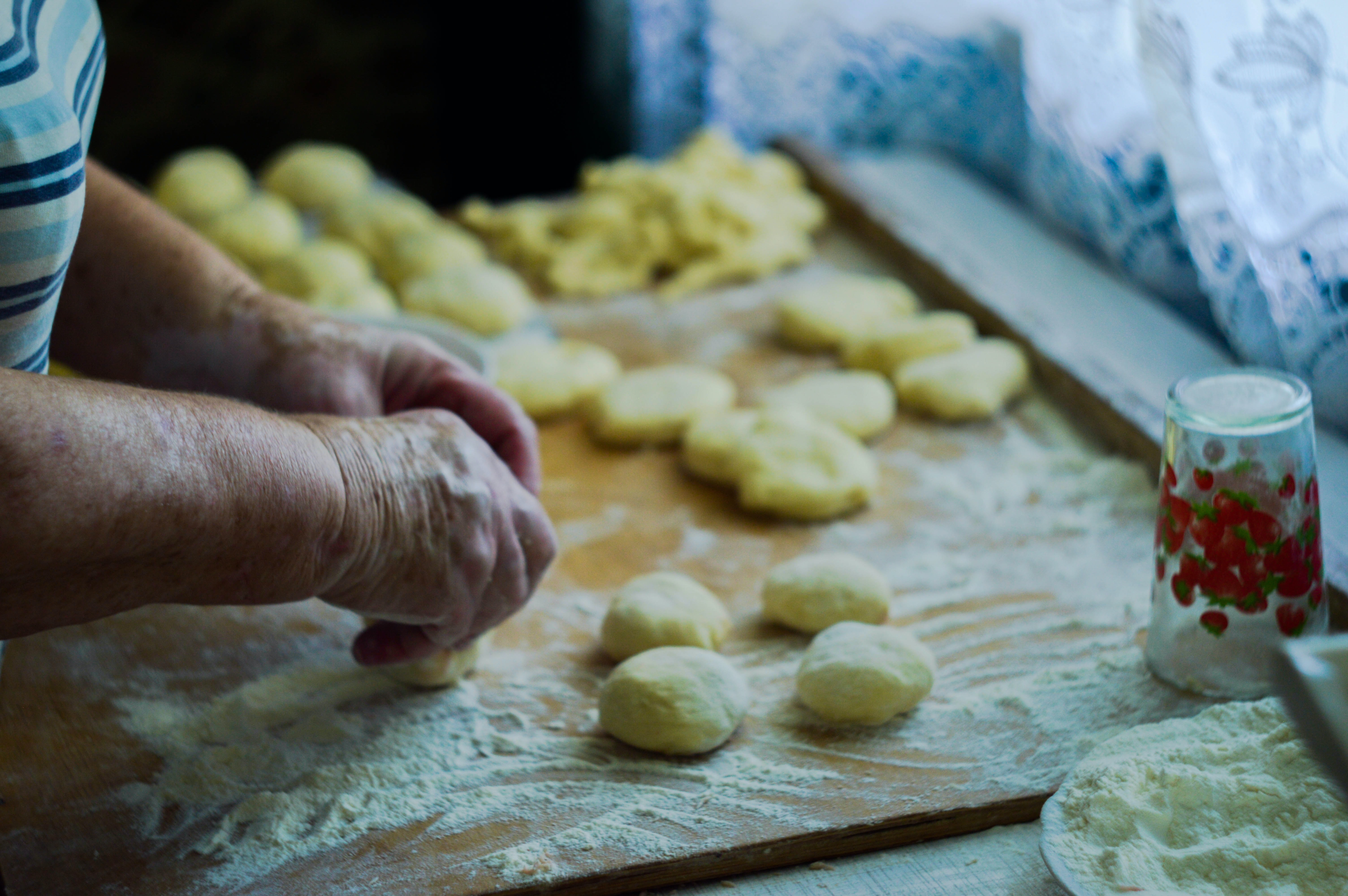 person making dough on brown wooden board