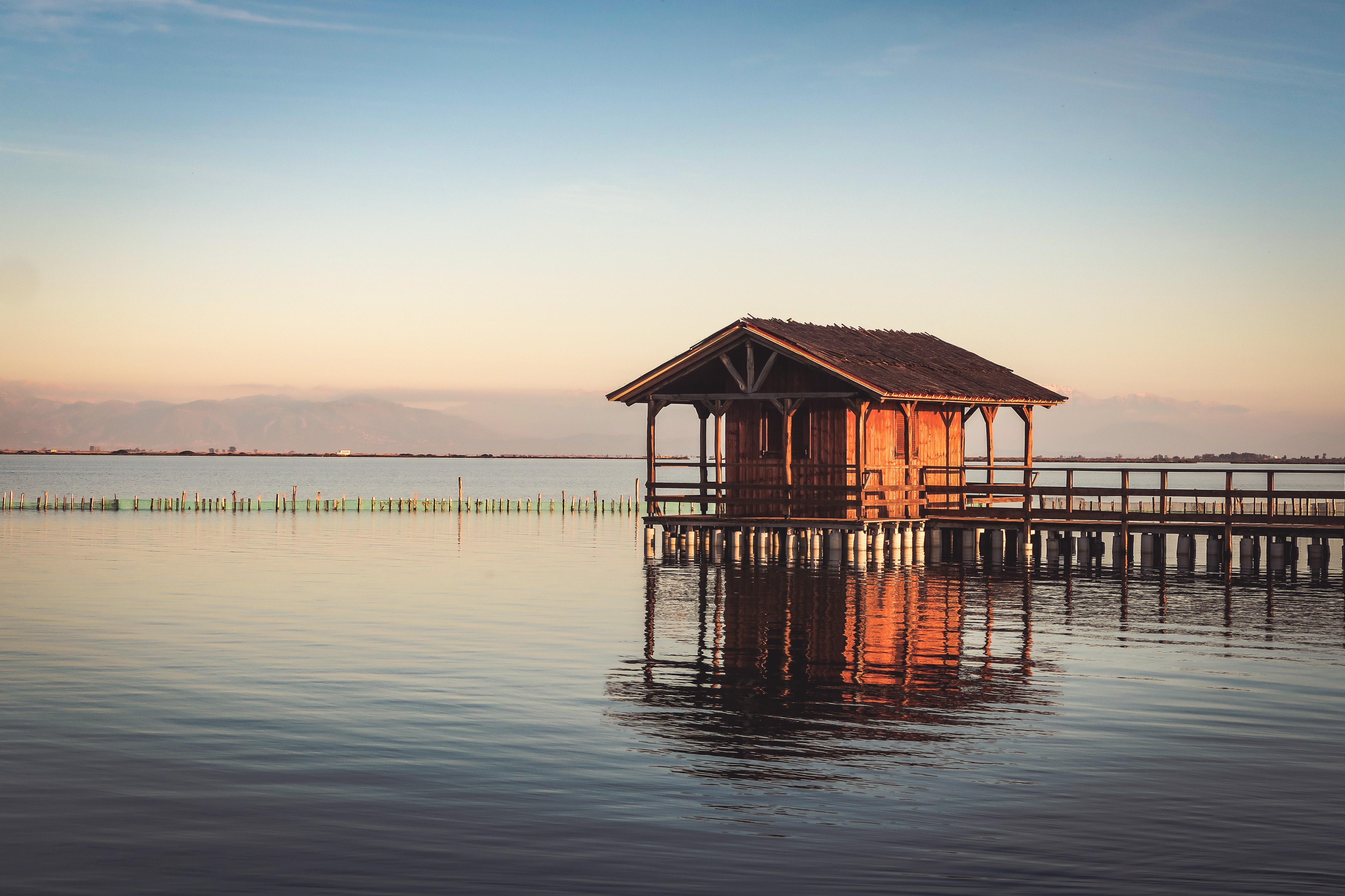brown wooden cottage on body of water