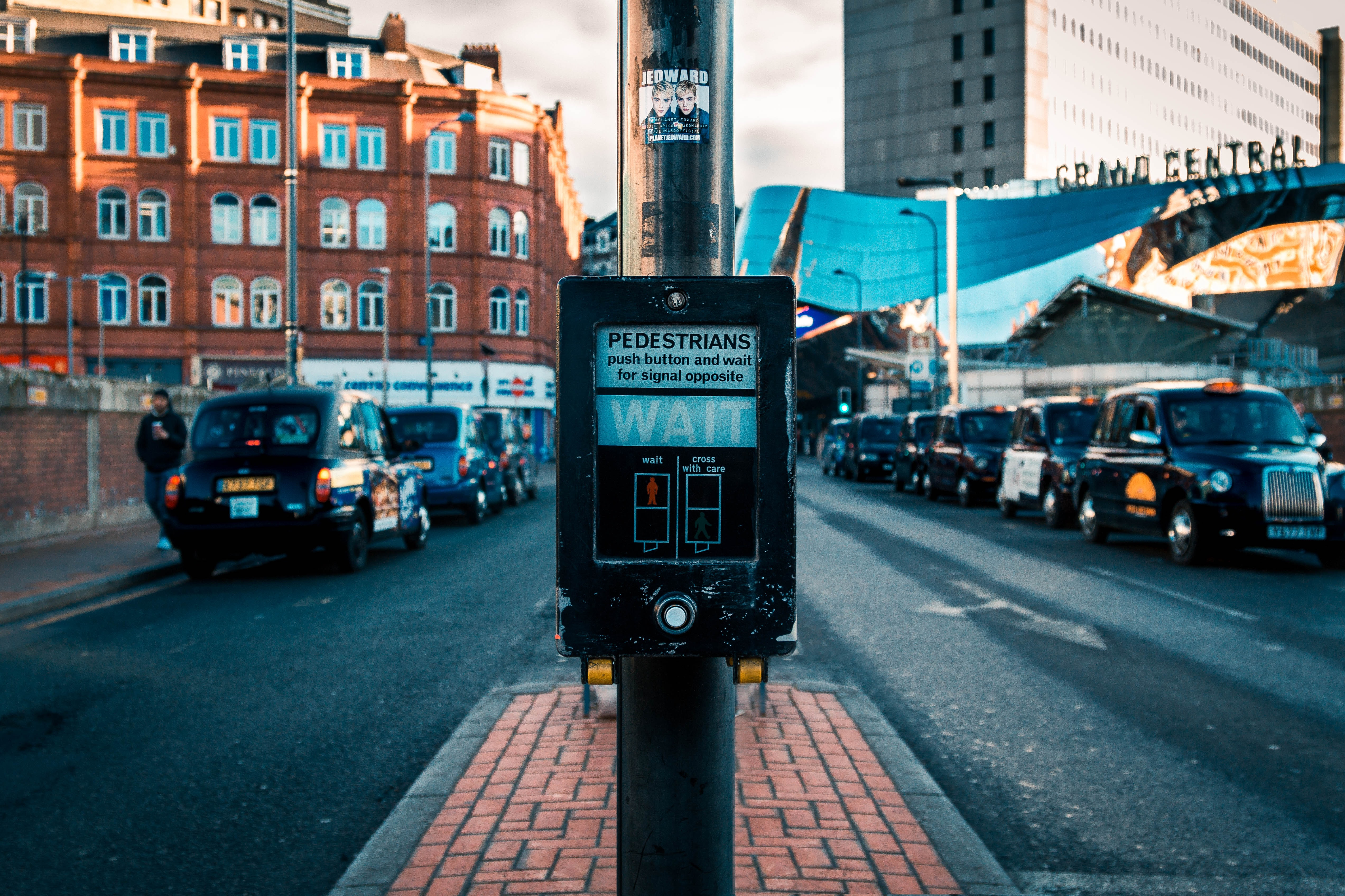 selective focus photography of pedestrians control knob between road during daytime