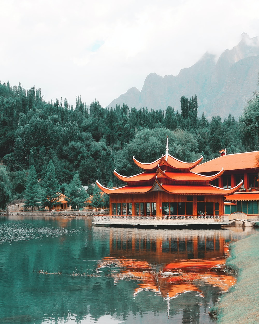 orange wooden building near green trees at daytime
