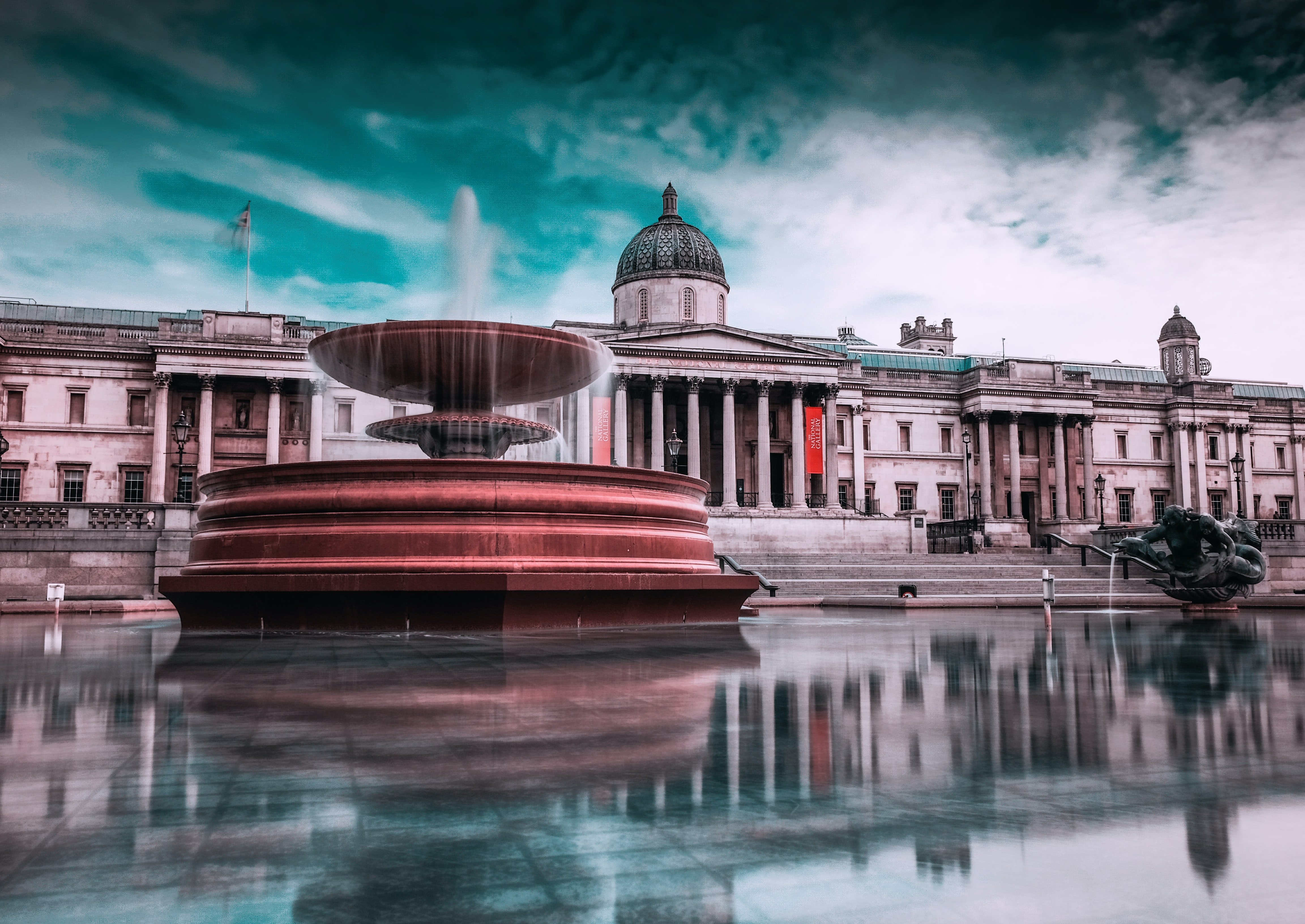 a fountain in trafalgar square with the national gallery in the background