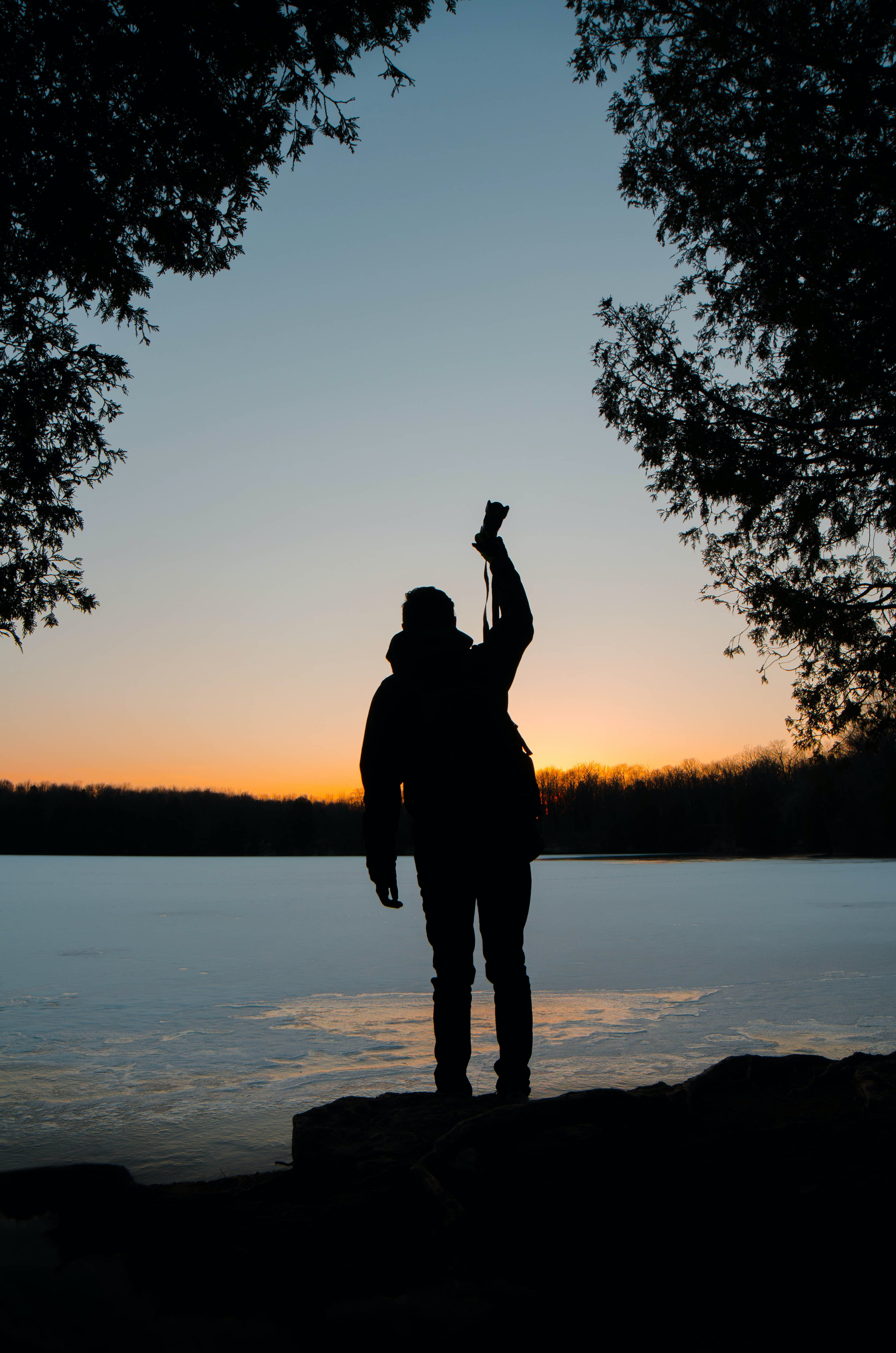 silhouette of person raising his right hand