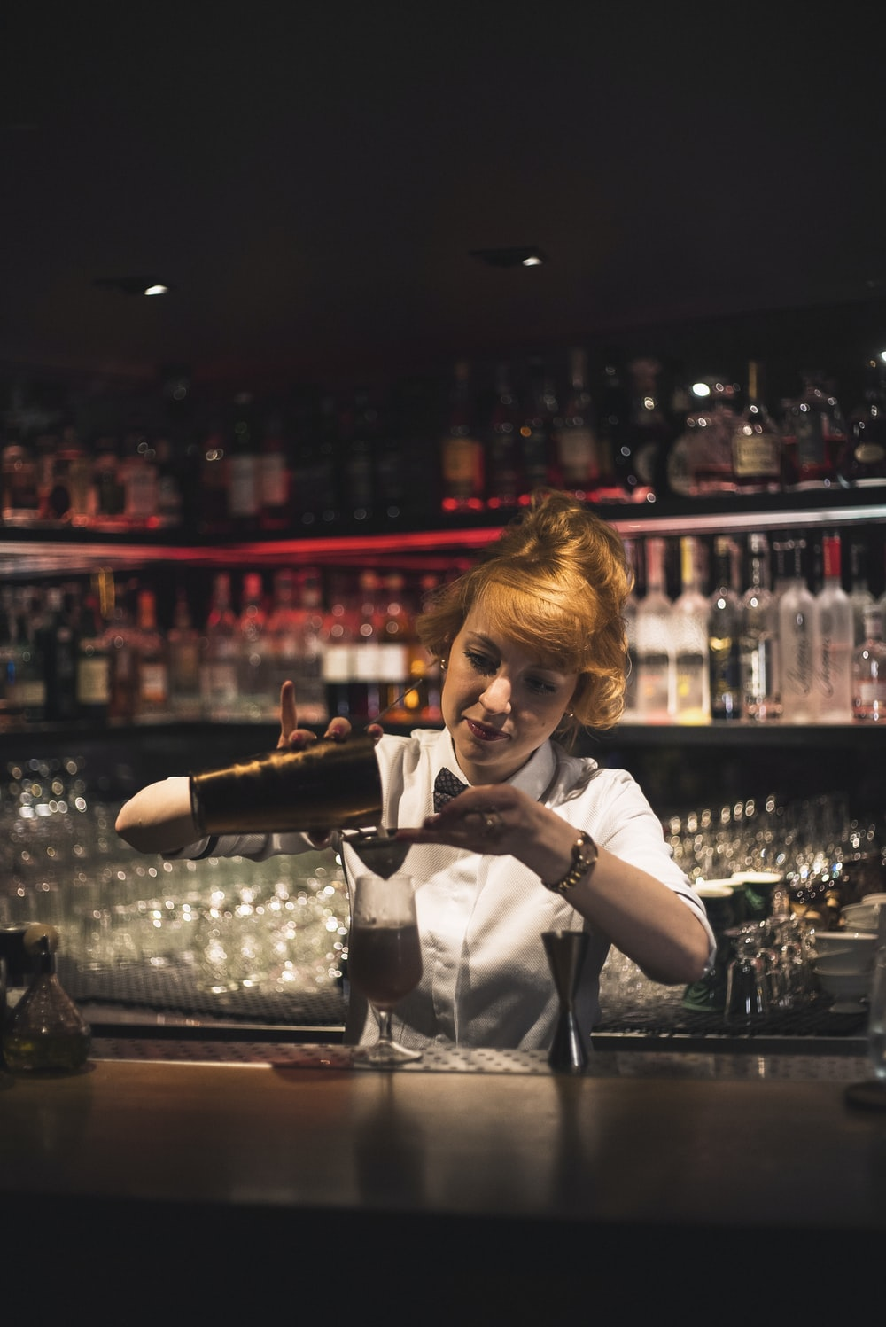 woman pouring bar shaker in clear glass stem glass on bar counter