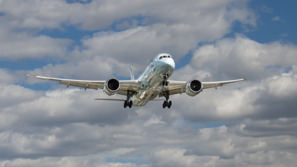 airliner flying under white clouds during daytime