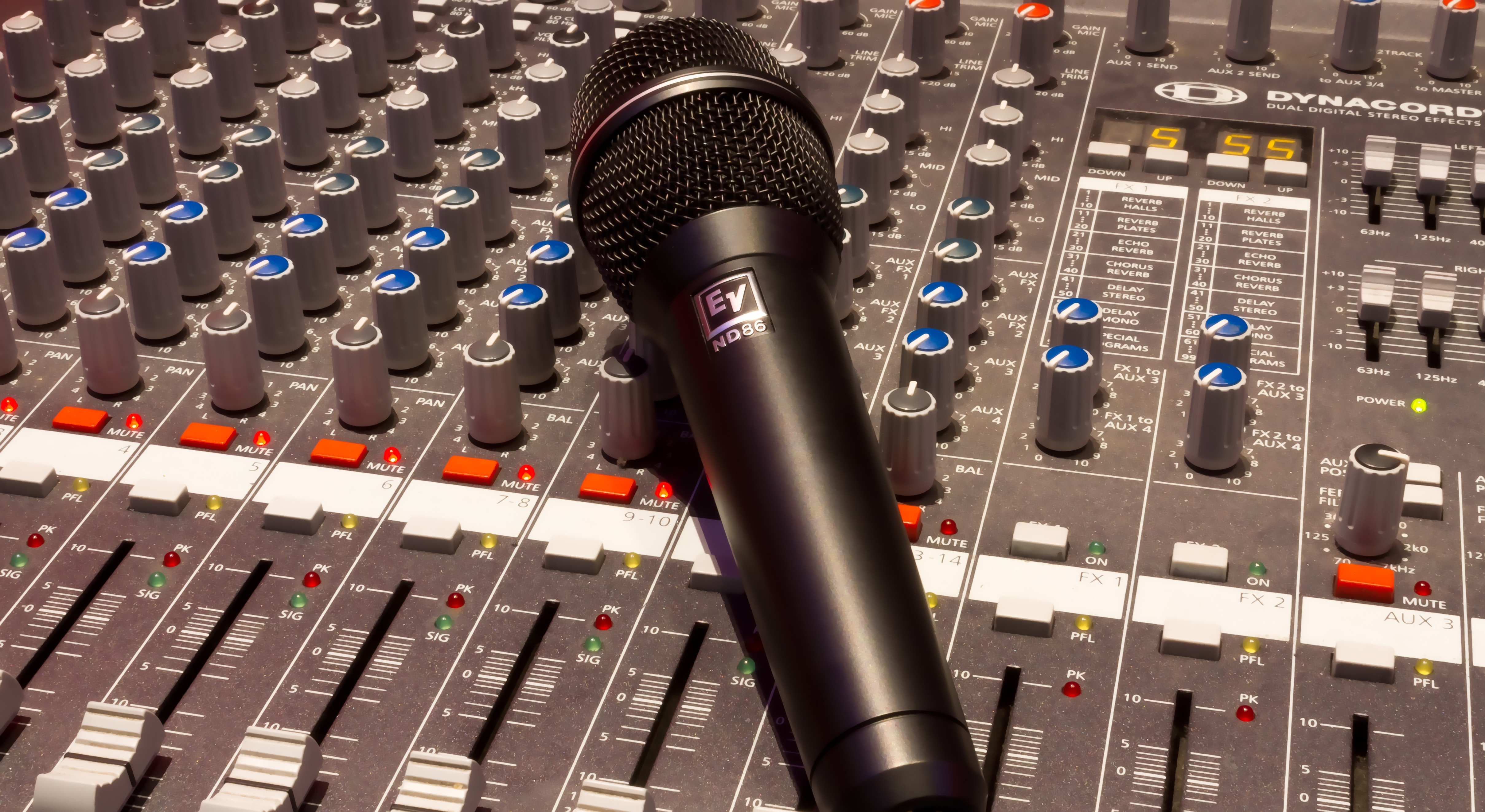 black wireless microphone on grey and multicolored audio mixer