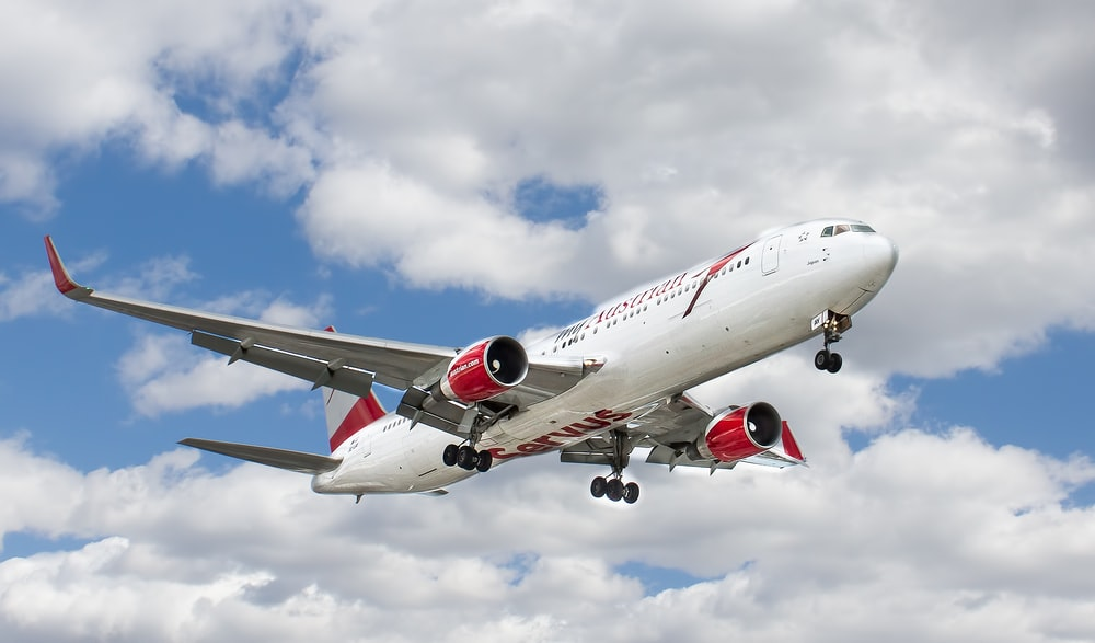 white and red flying airplane under white clouds